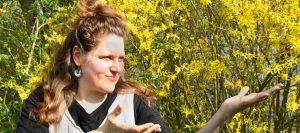 Mirjam steht in deutender Haltung for einem Forsythienstrauch